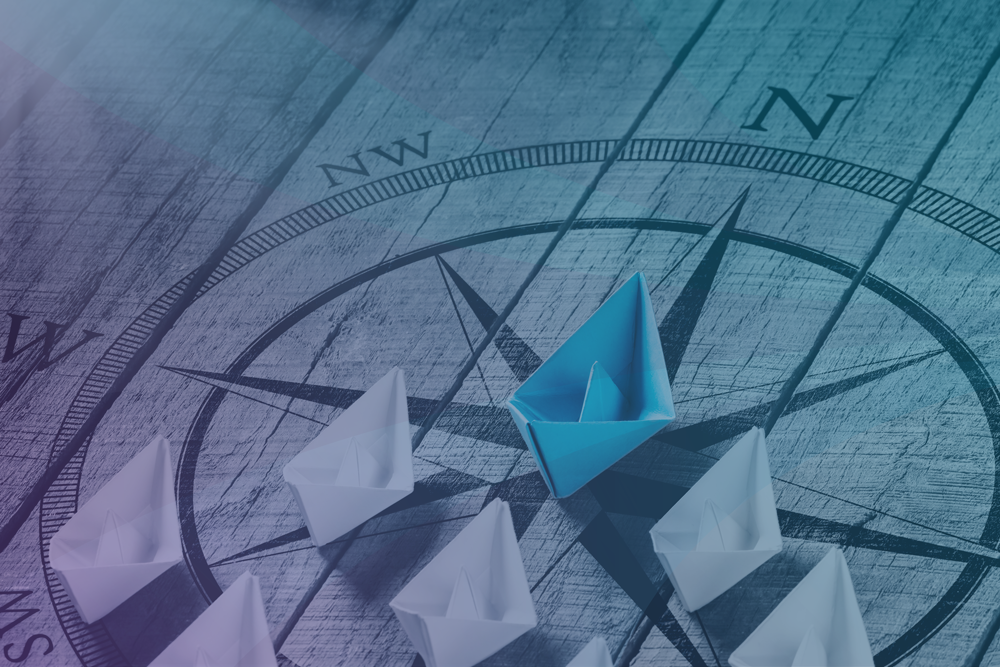 Leadership Image Showing A Compass With White Paper Boats Following A Blue Paper Boat